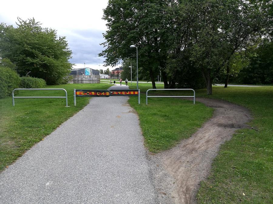 Path through grass going around barrier