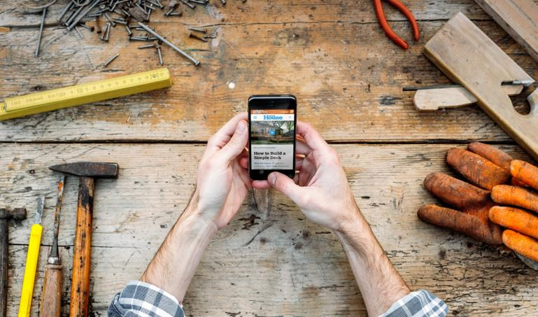 Hands holding smartphone over a workbench