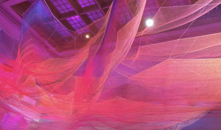 Large netting hanging above with vibrant colors of pink, purple and reds