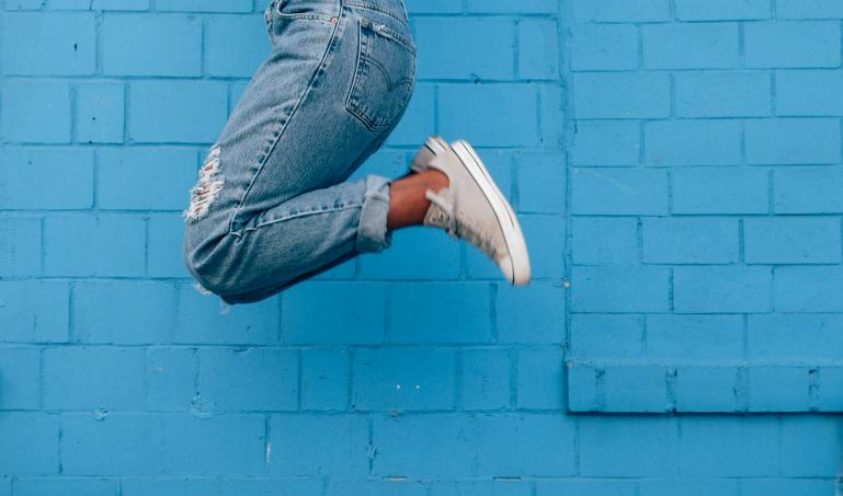 Lower half of a person jumping in front of a blue wall.