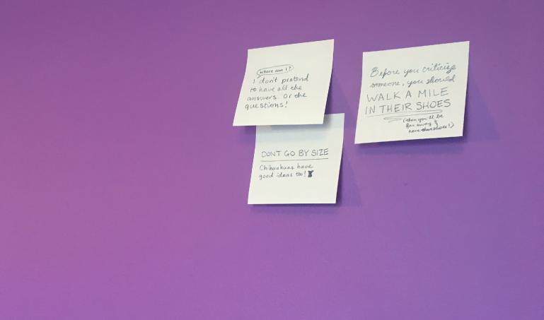 three hand-written post-its on a purple office wall